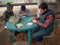 Crafters making seed necklaces
